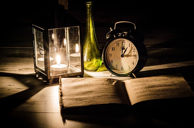 old book on desk with clock and lantern