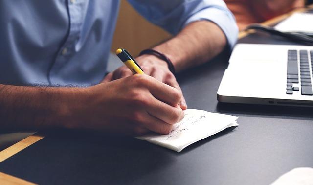 man writing next to laptop