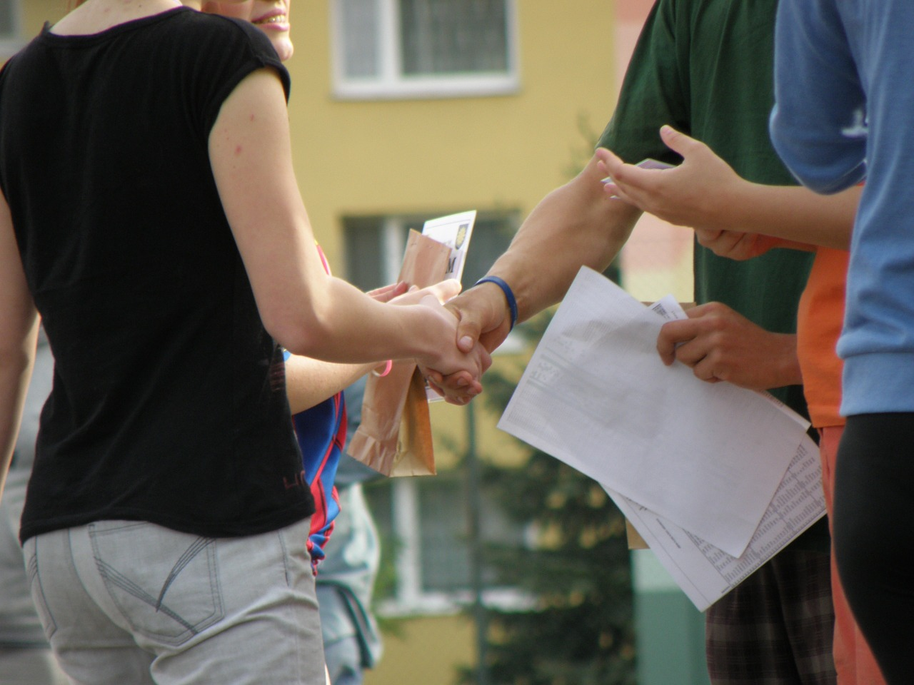Real estate agent shaking hands with clients