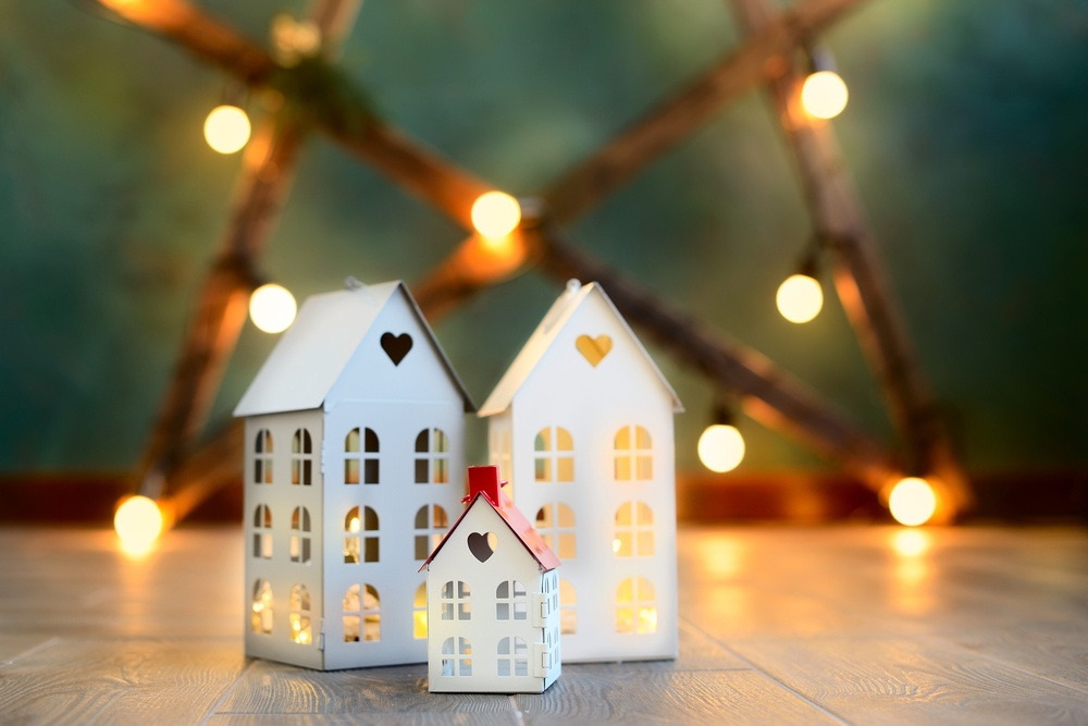 3 paper homes in front of holiday decoration